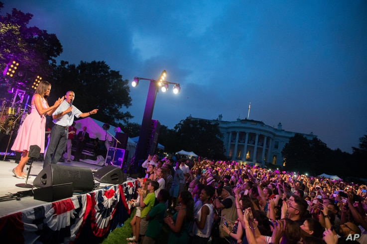 President Barack Obama, accompanied by first lady Michelle Obama, delivers remarks during an Independence Day celebration on the South Lawn at the White House in Washington, July 4, 2015.