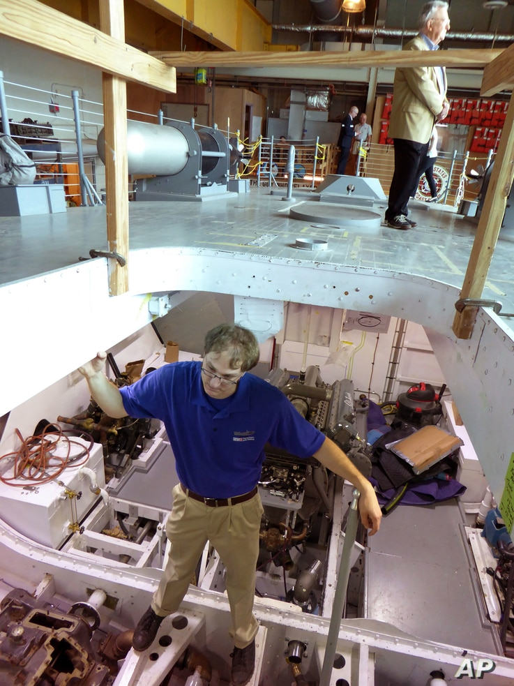 Josh Schick, project historian for the National World War II Museum, stands inside the engine room of PT-305, a World War II patrol torpedo boat being restored at the National World War II Museum in New Orleans, March 8, 2016.