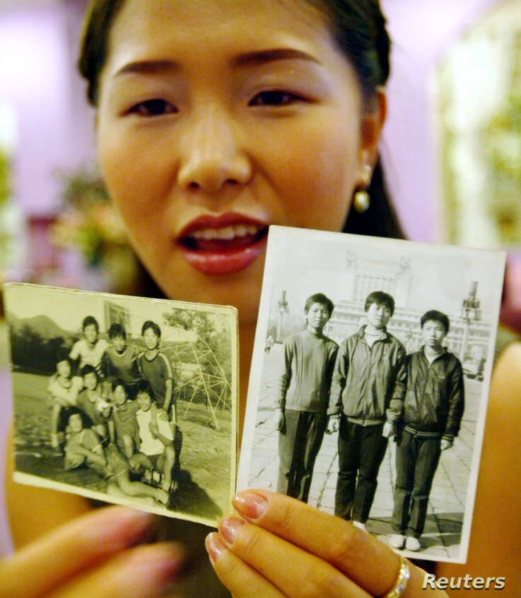 FILE - North Korean defector Hwangbo Young shows pictures of her friends taken in North Korea, June 17, 2003, in Seoul, South Korea. Hwangbo, 24, a promising teenage ice hockey player, escaped North Korea's economic spiral in 1997 to settle with her ...