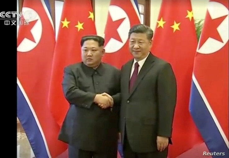 North Korean leader Kim Jong Un shakes hands with Chinese President Xi Jinping, in this still image taken from video released March 28, 2018.