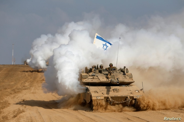 An Israeli soldier gestures from atop a tank after crossing the border back into Israel August 5, 2014. Israel pulled its ground forces out of the Gaza Strip on Tuesday and started a 72-hour ceasefire with Hamas mediated by Egypt as a first step towa...