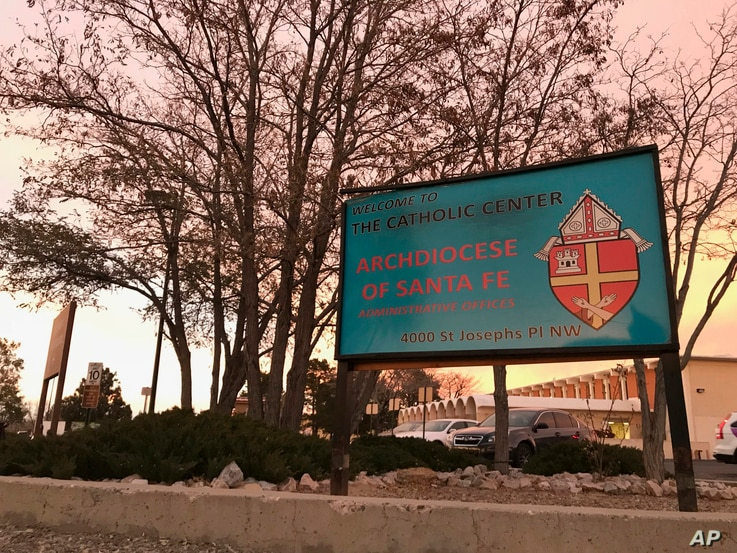 The sun sets on a sign in front of the Archdiocese of Santa Fe offices in Albuquerque, N.M., Nov. 29, 2018. Archbishop John Wester announced Thursday that the archdiocese will be filing for Chapter 11 bankruptcy protection, as the Catholic church in ...