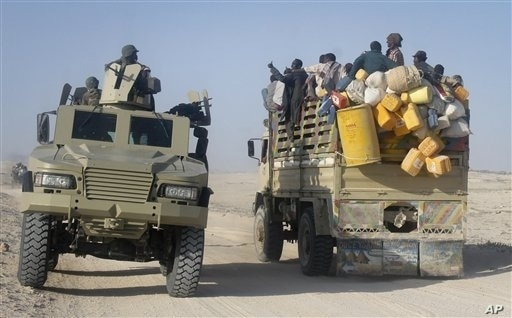 East African civilians depart in a truck, right, as AMISOM forces advance on al-Shabab-controlled region, Somalia, Sept. 4, 2012.