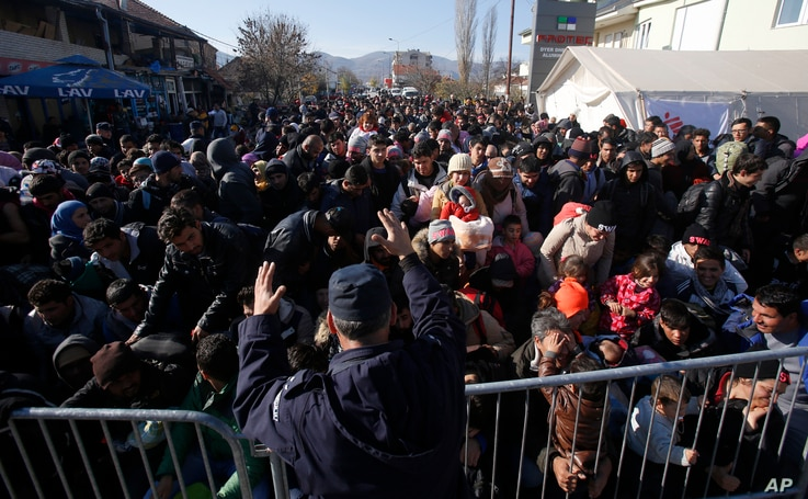 Serbian police officer attempt to organise migrants queuing to get registered at a refugee center in the southern Serbian town of Presevo, Monday, Nov. 16, 2015.