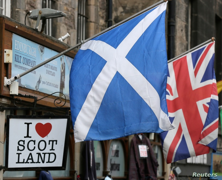 FILE - The Scottish Saltire flag (L) and the British Union flag are seen outside a shop in the centre of Edinburgh, Scotland on Sept. 12, 2014.