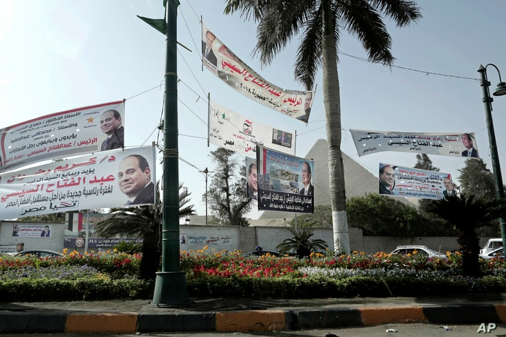 Election campaign banners for Egyptian presidential candidate President Abdel-Fattah el-Sissi hang in front of the Giza Pyramids, in Egypt, Monday, March 19, 2018.