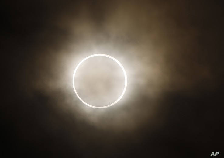 The moon slides across the sun, showing a blazing halo of light, during an annular eclipse at a waterfront park in Yokohama, near Tokyo, May 21, 2012.