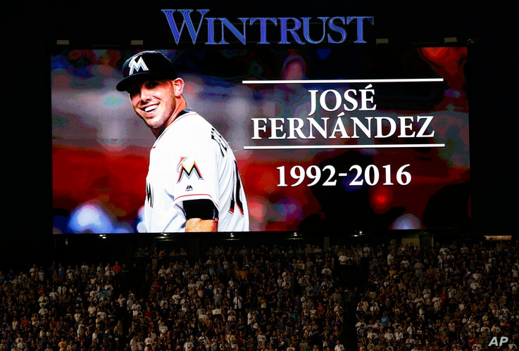Baseball fans stand for a minute of silence for Miami Marlins pitcher Jose Fernandez, who was killed early Sunday, Sept. 25, 2016 in a boating accident in Miami, before a baseball game between the St. Louis Cardinals and the Chicago Cubs Sunday, Sept...