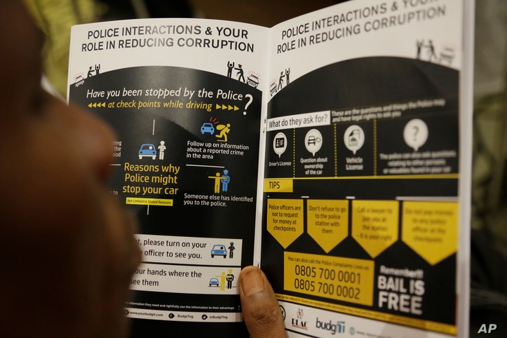 A man in Lagos, Nigeria, reads a booklet with guidelines for a web-based platform allowing people to report everyday corruption in Nigeria, Africa's populous nation. The United States government teamed up with Nigerian groups in July 2017 to launch t...