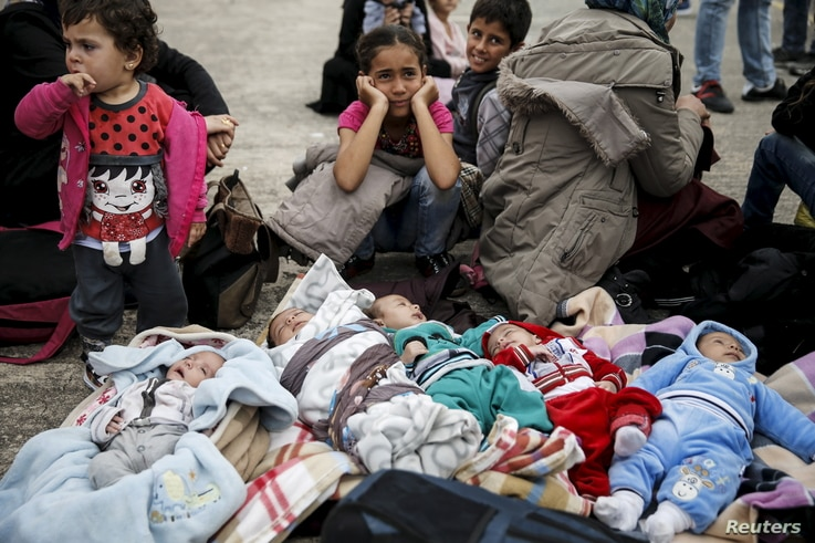 Five Syrian babies, three of them triplets, lie on blankets among relatives following the arrival of migrants from the islands of Lesbos and Chios at the port of Piraeus, near Athens, Greece, Oct. 21, 2015.