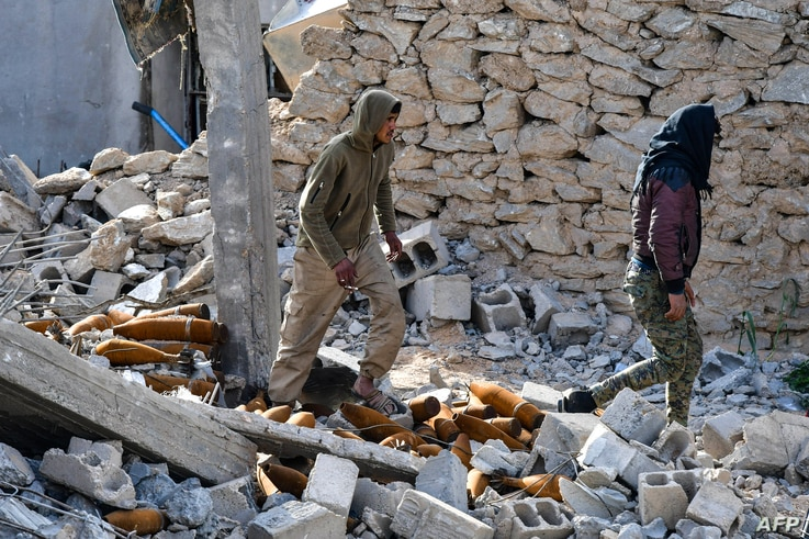 Fighters of the US-backed Kurdish-led Syrian Democratic Forces  walk through debris and mortar shells in the village of Baghuz in the eastern Syrian province of Deir Ezzor on March 21, 2019.