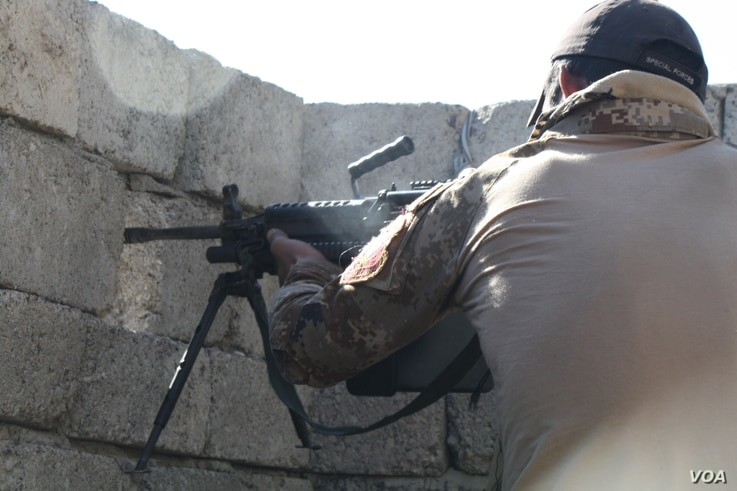 An Iraqi soldiers fires at a nearby house they believe IS may be planning to attack from on Nov. 19, 2016 in Mosul, Iraq.