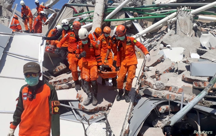 A search and rescue team evacuates a victim from the ruins of the Roa-Roa Hotel in Palu, Central Sulawesi, Indonesia, Sept. 30, 2018 in this photo taken by Antara Foto.