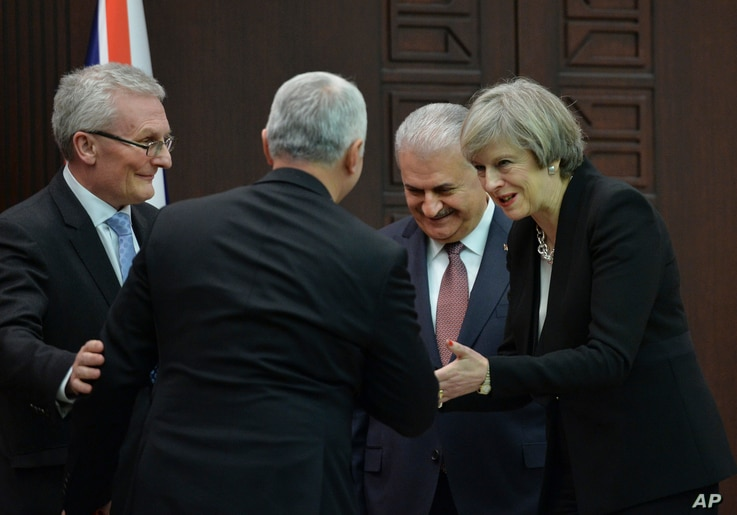 FILE - British Prime Minister Theresa May (R)  talks to Temel Kotil (back on camera), CEO of Turkish Aerospace industries, as Turkey's Prime Minister Binali Yildirim (2nd-R) and Ian Graham King (L), CEO of BAE Systems, look on after signing an agreem...