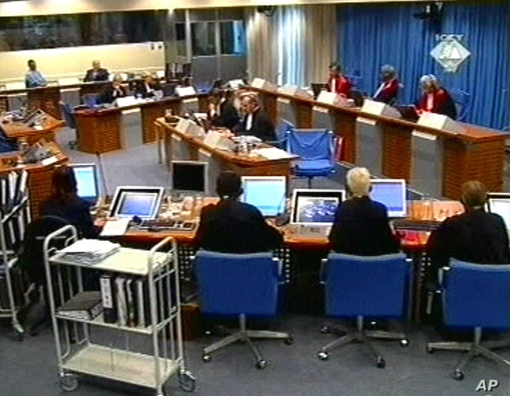 FILE - In this Tuesday Sept. 7, 2004, image made from TV, Slobodan Milosevic, second from top left, appears before the International Criminal Tribunal for the former Yugoslavia in The Hague, Netherlands.