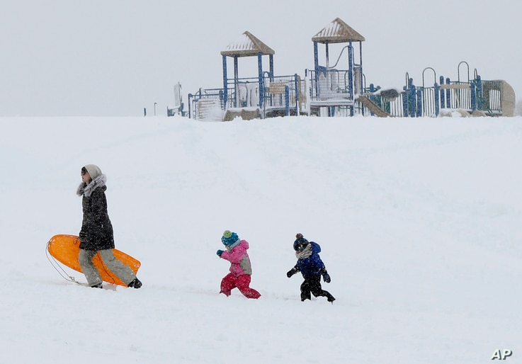 Christina Mesavage leads family friend, Una Mayer, center, and her son, Jude, up a sledding hill at the Eastern Promenade while enjoying the snow, March 8, 2018, in Portland, Maine.
