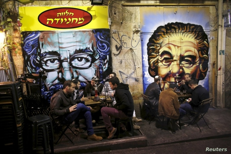 People dine near portraits of Albert Einstein (L) and former Israeli Prime Minister Golda Meir (R), spray-painted on metal shutters of closed storefronts in Mahane Yehuda, one of Jerusalem's most popular outdoor markets, Feb. 24, 2016.