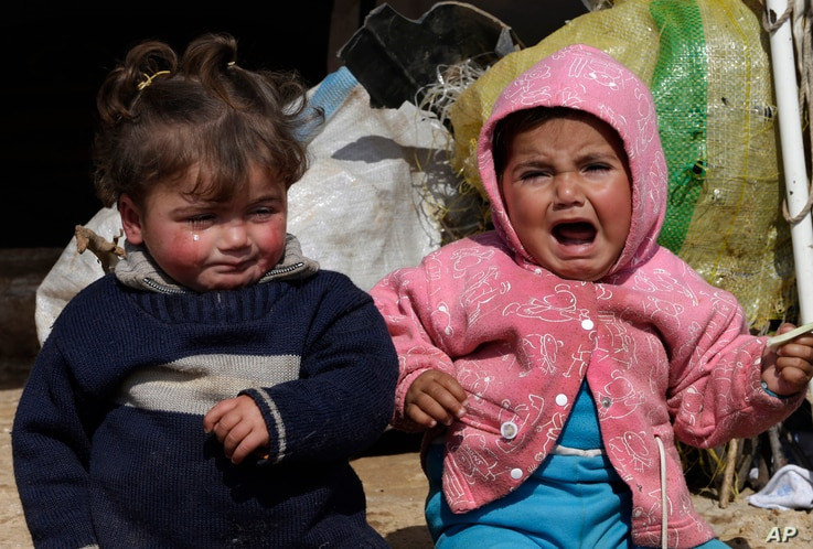 In this Tuesday, Feb. 19, 2013 photo, two Syrian refugee children sit outside their family tent, at Atmeh refugee camp, in the northern Syrian province of Idlib, Syria. This rebel-controlled camp only yards from the border with Turkey houses some 16,...
