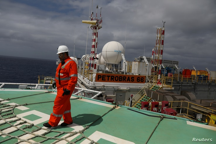 FILE - A worker walks on the heliport at the Brazil's Petrobras P-66 oil rig in the offshore Santos basin in Rio de Janeiro, Brazil, Sept. 5, 2018.