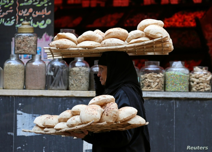 A woman carries bread as she leaves a bakery in Cairo, Egypt Jan. 10, 2017.