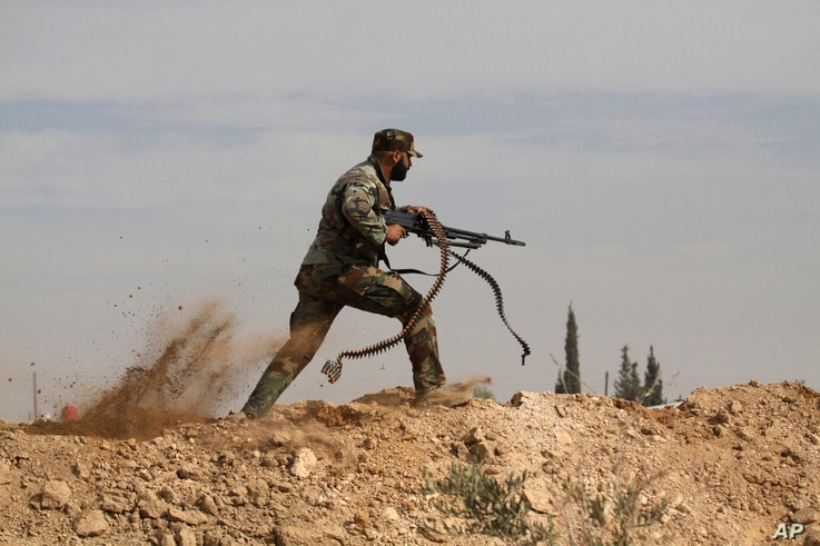FILE - Shiite fighter clashes with members of the Sunni-dominated Free Syrian Army rebel in the town of Hatita, in the countryside of Damascus, Syria.