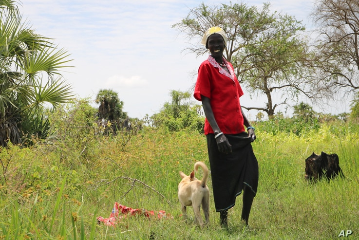 In this photo taken Wednesday, Aug. 15, 2018, 40-year-old mother of five Mary Nyataba stands with her dog on Raath island, off the mainland from the opposition-held town of Nyal in Unity state, in South Sudan.