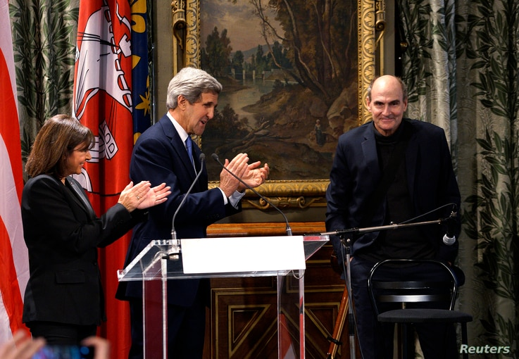 Mayor of Paris Anne Hidalgo and U.S. Secretary of State John Kerry applaud a performance by singer James Taylor at City Hall in Paris, Jan. 16, 2015.