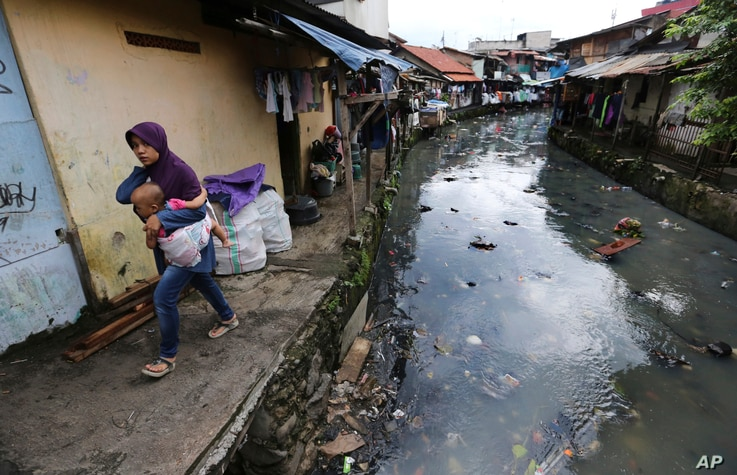 A woman carrying a child walks along a garbage-strewn river at a slum in Jakarta, Indonesia, April 3, 2017. Most of Jakarta's waterways are polluted, contributing not only to a lack of clean water, but also making flooding more likely during the rain...