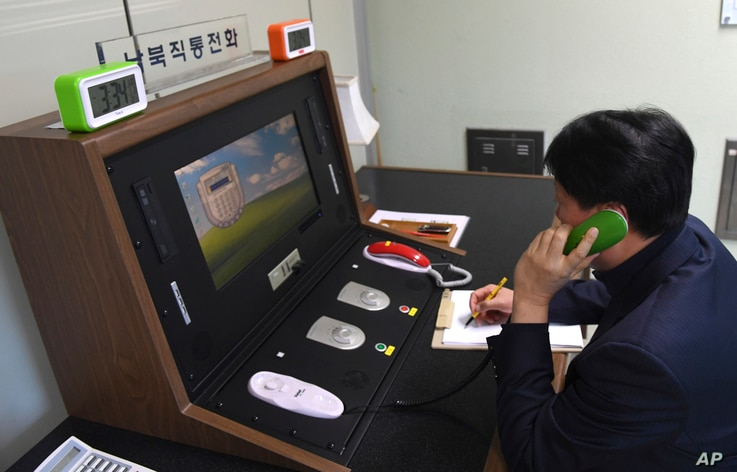 In this photo provided by South Korea Unification Ministry, a South Korean government official communicates with a North Korean officer during a phone call on the dedicated communications hotline at the border village of Panmunjom in Paju, South Kore...