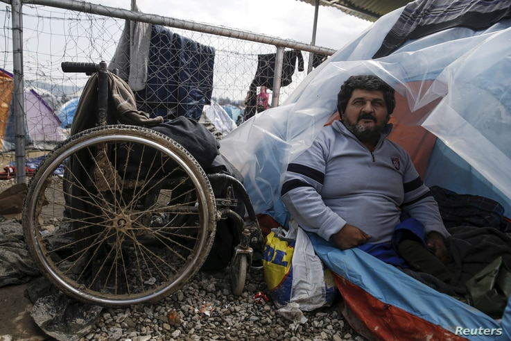 Iraqi refugee Hassan Omar, 48, poses inside his tent next to his wheelchair at a makeshift camp for refugees and migrants at the Greek-Macedonian border near Idomeni, Greece, March 17, 2016.