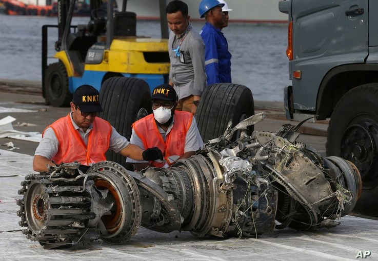 FILE - Officials inspect an engine recovered from the crashed Lion Air jet in Jakarta, Indonesia, Nov. 4, 2018. The brand new Boeing 737 MAX 8 jet plunged into the Java Sea just minutes after takeoff from Jakarta early on Oct. 29, killing all passeng...