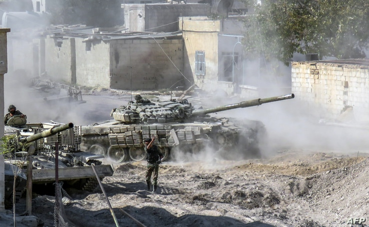 A Syrian Army modified T-72 tank drives during Syrian forces' assault to capture the rebel-held village of Hawsh Nasri, which is located near the rebel-held town of Douma on the eastern outskirts of the capital Damascus, Nov. 22, 2016.