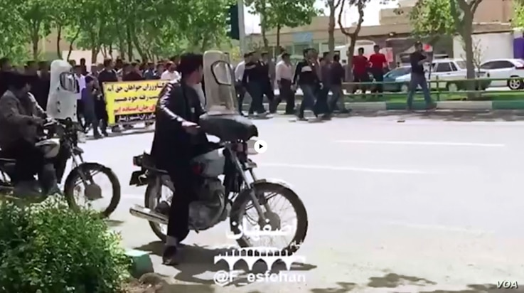 In this frame from a social media video posted April 13, 2018, people in Khorasgan, Iran march to protest water shortages that are hurting local farmers.