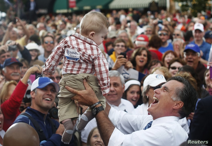 Republican presidential nominee Mitt Romney holds a baby up in the air after a campaign rally at the Golden Lamb in Lebanon, Ohio October 13, 2012.