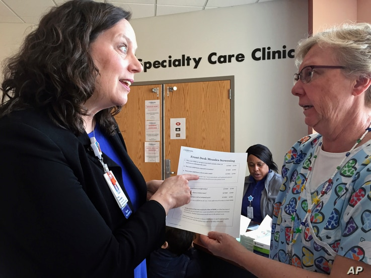 FILE - In this May 2, 2017 photo, Patsy Stinchfield, left, senior director of infection control at Children's Minnesota in Minneapolis, talks with nurse Kathy Kaul about a measles screening questionnaire that hospital staff are using to assess a pati...