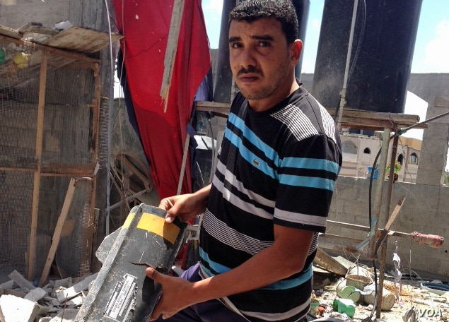 Anwar Mohammed holds part of a rocket that destroyed his family's home in Gaza during Israel's Operation Protective Edge targeting Palestinian militants. Photo VOA / Gabe Joselow