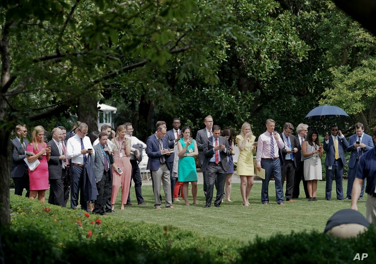 FILE - Journalists wait in the Rose Garden of the White House in Washington, for the signal to proceed forward as they wait to attend a statement by President Donald Trump and European Commission president Jean-Claude Juncker, July 25, 2018.