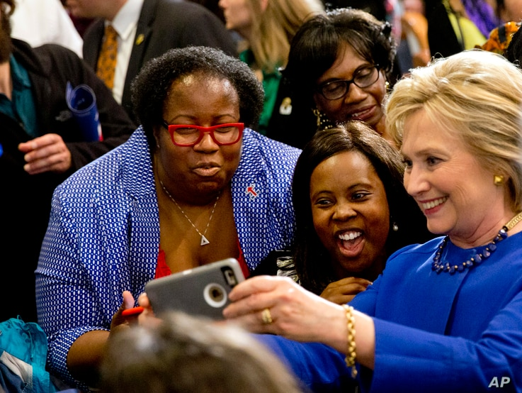 FILE - Democratic presidential candidate Hillary Clinton takes pictures with supporters after a campaign event at the Central Baptist Church in Columbia, S.C.,  Feb. 23, 2016, during a primary season that has proved surprisingly competitive.
