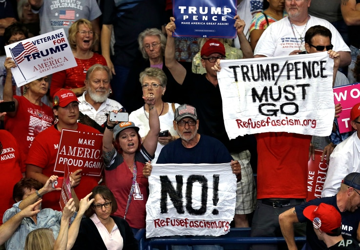 Protesters hold up signs during a rally as President Donald Trump speaks at the Covelli Centre in Youngstown, Ohio, July 25, 2017.