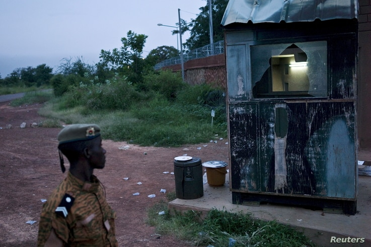 A soldier surveys damage caused by fighting after the Burkinabe army took control of the Naaba Koom military camp in Ouagadougou, Burkina Faso, Sept. 30, 2015.
