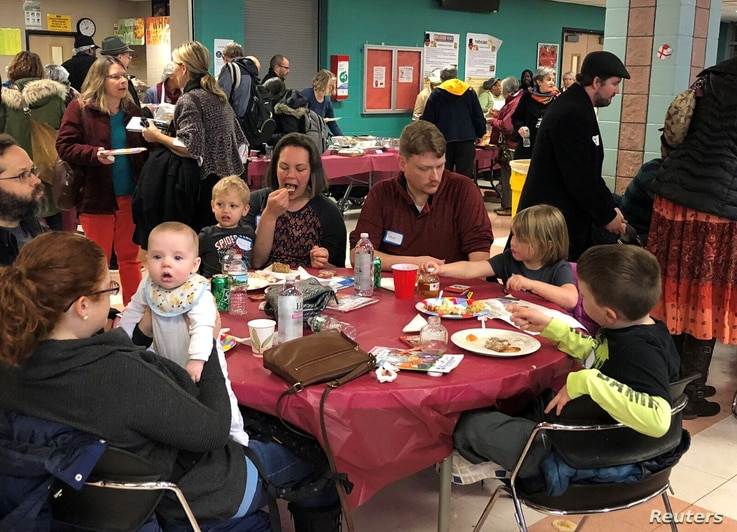 Furloughed government workers, contractors and their families attend a free community dinner donated from families and community organizations during the partial U.S. government shutdown at Montgomery Blair High School in Silver Spring, Md., Jan. 11,...