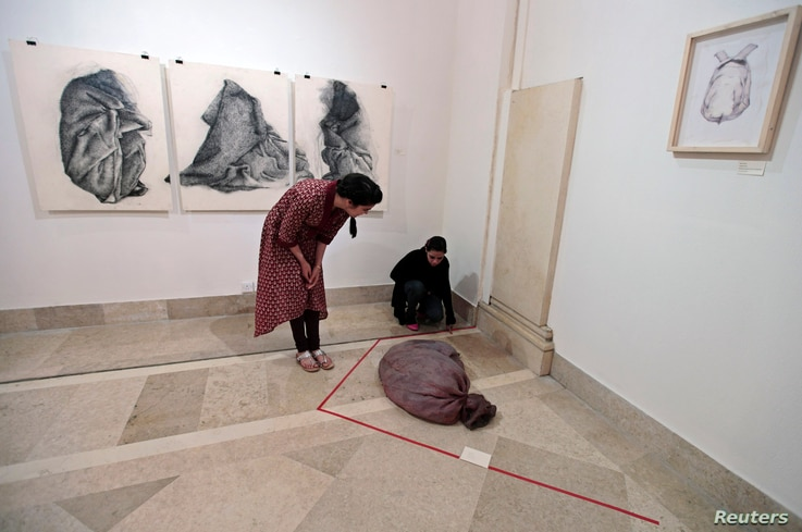 Visitors look at a latex russet-colored sack designed to feel like human skin, at an exhibition in Islamabad, Pakistan, April 3, 2013.