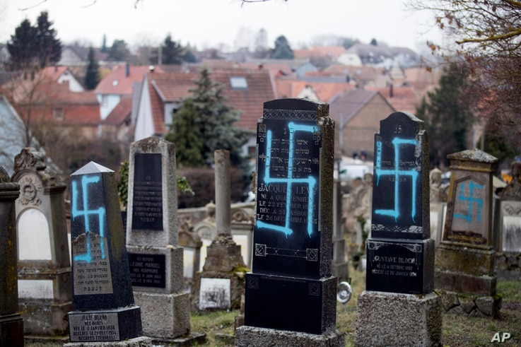 FILE - Vandalized tombs with tagged swastikas are pictured in the Jewish cemetery of Quatzenheim, eastern France, Feb.19, 2019.