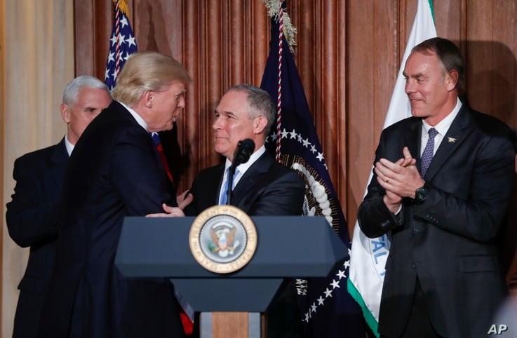 President Donald Trump shakes hands with EPA Administrator Scott Pruitt, flanked by Vice President Mike Pence and Interior Secretary Ryan Zinke,  March 28, 2017, at EPA headquarters in Washington.