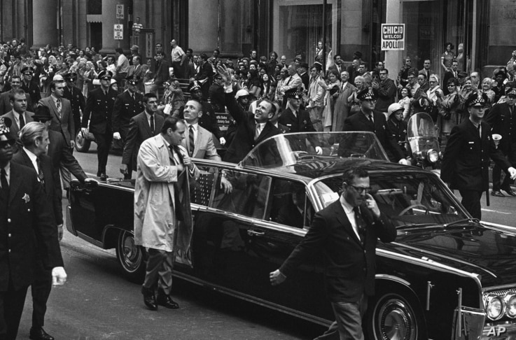 Apollo 13 astronauts John Swigert Jr., with his arms upraise and James Lovell ride in parade in their honor, Friday, May 2, 1970 through Chicago's financial district as confetti streams from the skyscrapters. (AP Photo)