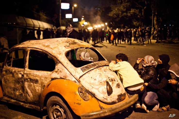 An Egyptian protester take cover beside a vehicle damaged during clashes between protesters and Egyptian security forces in Cairo, Egypt, January 28, 2013.