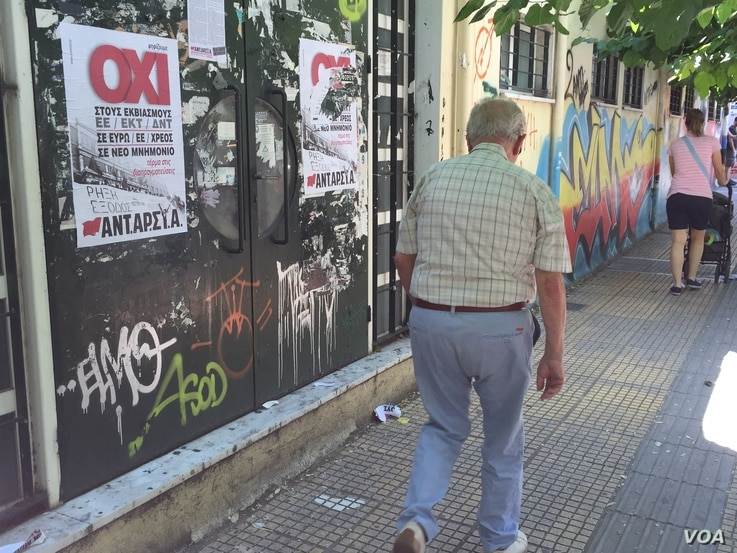"""A man walks past a """"No"""" campaign poster during a referendum in central Athens, Greece, July 5, 2015."""