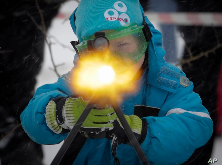 A boy to shoots a machine gun with blanks, at a weapon exhibition during a military show outside St.Petersburg, Russia, Jan. 15, 2017.