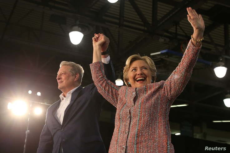 U.S. Democratic presidential nominee Hillary Clinton (R) and former Vice President Al Gore shake hands after talking about climate change at a rally at Miami Dade College in Miami, Florida, U.S. Oct. 11, 2016.