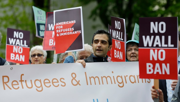 Protesters hold signs during a demonstration against President Donald Trump's revised travel ban, May 15, 2017, outside a federal courthouse in Seattle.
